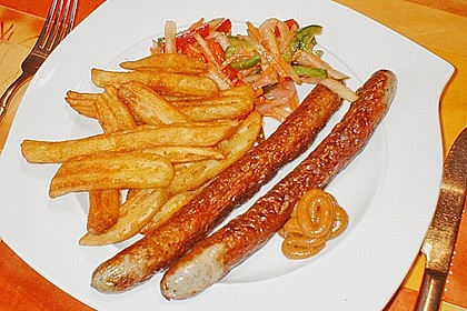 Schlangenwurst mit frittierten Riffelkartoffeln an buntem Streifensalat