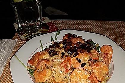 Bandnudeln Aglio e Olio mit Cocktailtomaten und Shrimps auf einem Bett aus Rucola