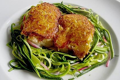 Blaulengmedaillons unter der Kartoffelkruste in einem Nest aus Zucchinistreifen