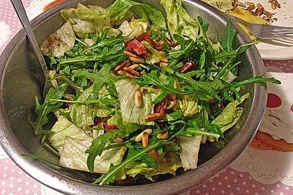 Salat mit Rucola, Pinienkernen und Schinkenfrischkäseröllchen